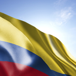 Flag of Colombia waving in the wind. Blue sunny sky in the background. Horizontal orientation.